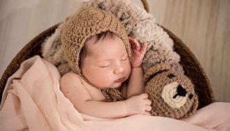 Baby sover i sin egen krybbe med bamse