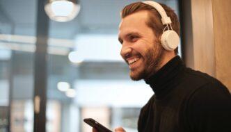 Glad mand hører musik på kontor