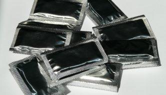 Grå eller sølv kondomer ligger på hvidt bord